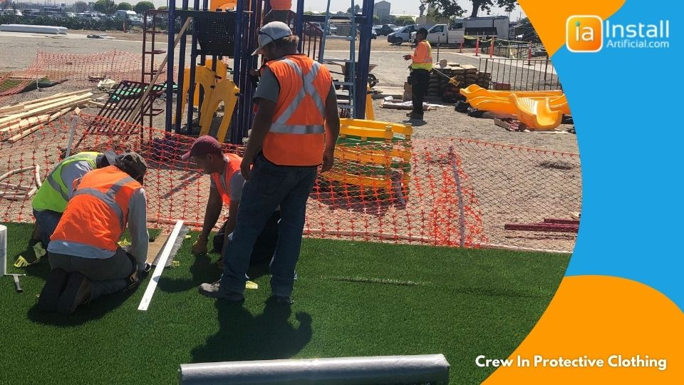 Artificial grass installation crew in protective clothing during install.