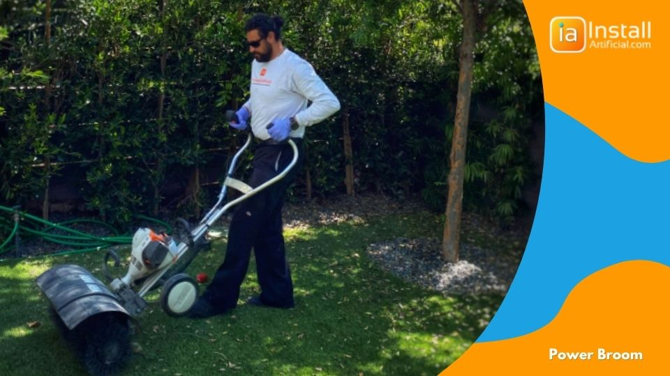 power brushing grass blades after artificial turf installation in backyard.