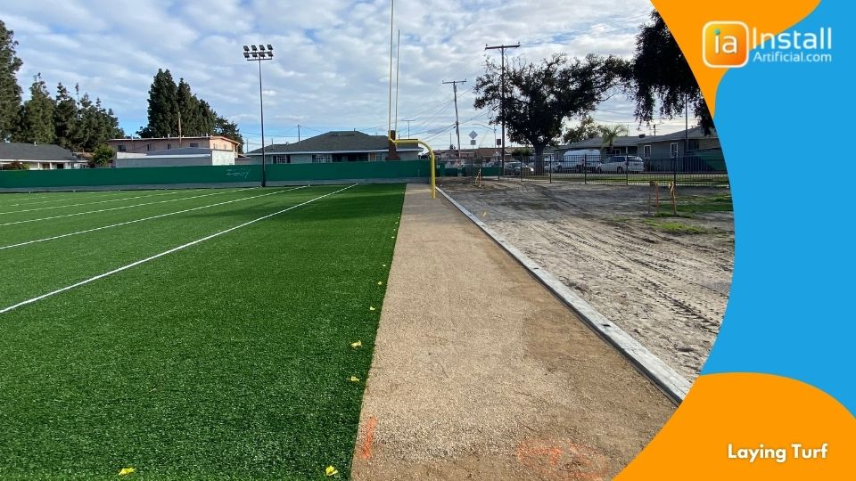 Laying artificial sports turf on the base of the field during installation